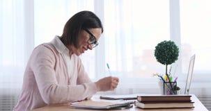 Donna di affari che per mezzo del computer portatile e facendo le note archivi video