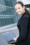 Donna di affari che per mezzo del computer portatile fuori dell'ufficio Immagine Stock