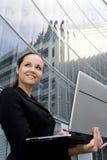 Donna di affari che per mezzo del computer portatile fuori dell'ufficio Fotografia Stock