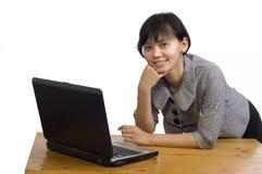 Donna di affari che per mezzo del computer portatile su priorità bassa bianca Fotografie Stock Libere da Diritti