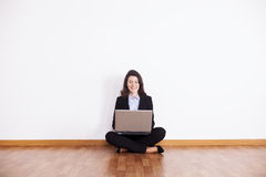Donna di affari che per mezzo del suo computer portatile Fotografia Stock
