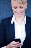 Donna di affari che per mezzo del telefono astuto Fotografia Stock