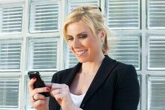 Donna di affari che per mezzo del telefono astuto Immagini Stock