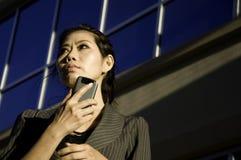 Donna di affari che per mezzo del telefono astuto delle cellule Fotografia Stock Libera da Diritti