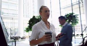Donna di affari che per mezzo del telefono cellulare e camminando nell'ingresso all'ufficio 4k video d archivio