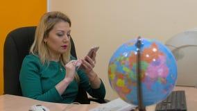 Donna di affari che per mezzo del telefono cellulare per Internet di lettura rapida sull'ufficio dell'area di lavoro archivi video