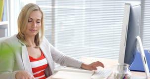 Donna di affari che per mezzo del telefono cellulare mentre lavorando al computer video d archivio