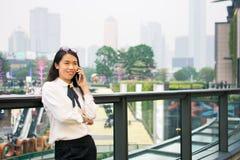 Donna di affari che per mezzo del telefono circondato dalle costruzioni moderne Fotografie Stock