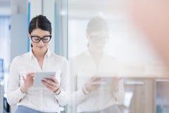Donna di affari che per mezzo della compressa di Digital davanti all'ufficio startup fotografia stock