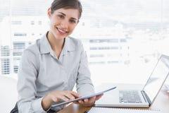 Donna di affari che per mezzo della compressa digitale che sorride alla macchina fotografica Immagine Stock