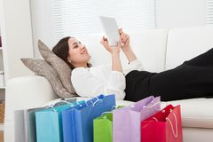 Donna di affari che per mezzo della compressa digitale con i sacchetti della spesa sul pavimento Immagini Stock Libere da Diritti