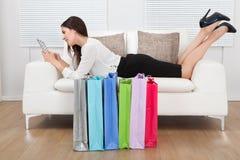 Donna di affari che per mezzo della compressa digitale con i sacchetti della spesa sul pavimento Fotografia Stock