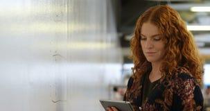 Donna di affari che per mezzo della compressa digitale mentre leggendo i dati 4k archivi video