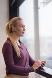 Donna di affari che per mezzo dello Smart Phone all'ufficio Fotografie Stock