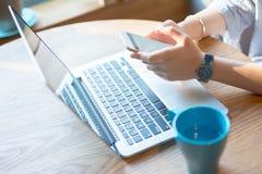 Donna di affari che per mezzo dello smartphone e del computer portatile Immagine Stock