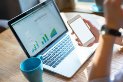 Donna di affari che per mezzo dello smartphone e del computer portatile Immagini Stock Libere da Diritti