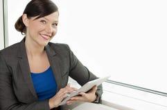 Donna di affari che per mezzo di un calcolatore del ridurre in pani Fotografia Stock