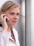 Donna di affari che per mezzo di un telefono mobile immagine stock