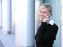 Donna di affari che per mezzo di un telefono mobile fotografia stock