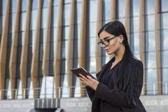 Donna di affari che per mezzo di una compressa digitale Immagini Stock