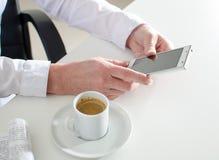 Donna di affari che per mezzo di uno smartphone durante la pausa caffè Fotografie Stock