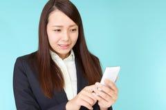 Donna di affari che per mezzo di uno Smart Phone fotografie stock libere da diritti