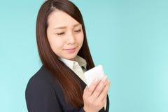 Donna di affari che per mezzo di uno Smart Phone fotografia stock