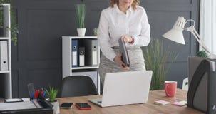 Donna di affari che prende archivio dallo scaffale e che per mezzo del computer portatile all'ufficio video d archivio