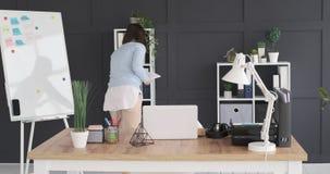 Donna di affari che prende archivio dallo scaffale e che ritorna alla sua scrivania video d archivio