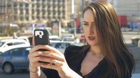 Donna di affari che prende i selfies con la macchina fotografica dello smartphone con la via del traffico cittadino nei precedent stock footage