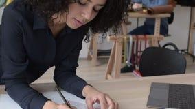 Donna di affari che prende le note e che per mezzo di un computer portatile stock footage