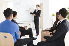 Donna di affari che presenta nuovo progetto ai partner in ufficio Immagine Stock