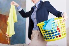 Donna di affari che raccoglie i vestiti sporchi Immagini Stock Libere da Diritti