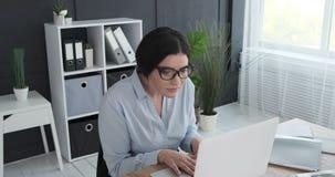 Donna di affari che riceve buone notizie sul computer portatile video d archivio
