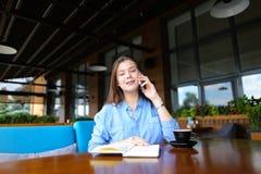 Donna di affari che riposa al caffè con il taccuino e la tazza di caffè, parlanti dallo smartphone Immagini Stock Libere da Diritti