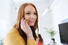 Donna di affari che rivolge allo smartphone all'ufficio Immagini Stock