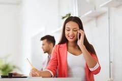 Donna di affari che rivolge allo smartphone all'ufficio Immagine Stock Libera da Diritti