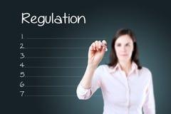 Donna di affari che scrive il fondo in bianco del blu della lista di regolamento Immagini Stock