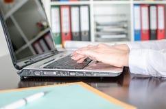 Donna di affari che scrive su un computer portatile Immagini Stock