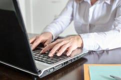 Donna di affari che scrive su un computer portatile Fotografia Stock Libera da Diritti