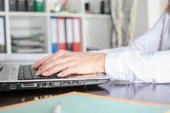 Donna di affari che scrive su un computer portatile Fotografia Stock