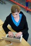 Donna di affari che scrive sul computer portatile in magazzino Fotografia Stock