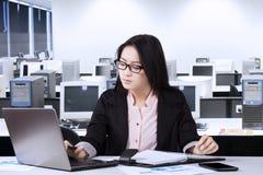 Donna di affari che scrive sul computer portatile nella stanza dell'ufficio Immagine Stock Libera da Diritti
