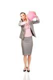 Donna di affari che scuote un porcellino salvadanaio Fotografia Stock Libera da Diritti