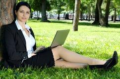 Donna di affari che si distende con il computer portatile Fotografia Stock