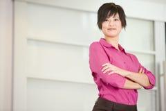 Donna di affari che si leva in piedi all'interno sorridente Fotografie Stock Libere da Diritti