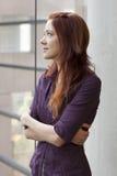 Donna di affari che si leva in piedi alla finestra che guarda verso l'alto Immagini Stock Libere da Diritti