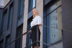 Donna di affari che si leva in piedi davanti all'edificio per uffici immagini stock