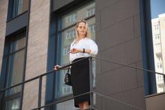 Donna di affari che si leva in piedi davanti all'edificio per uffici immagine stock libera da diritti