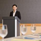 Donna di affari che si leva in piedi dietro il podio Fotografia Stock Libera da Diritti